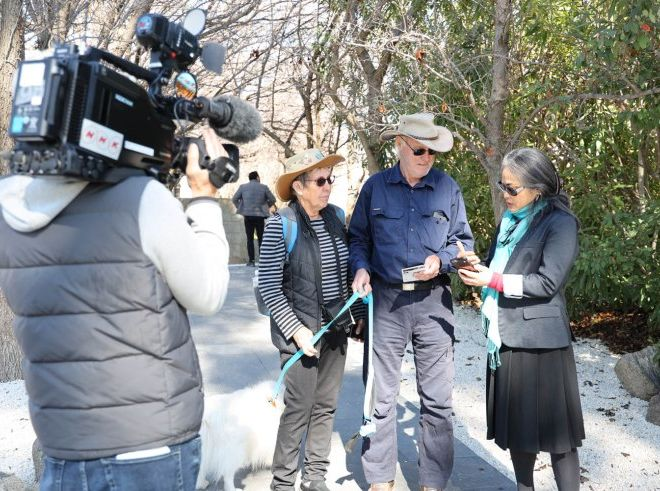 Masako Fukui showing Cowra Voices to visitors at Cowra Japanese Cemetery as NHK looks on